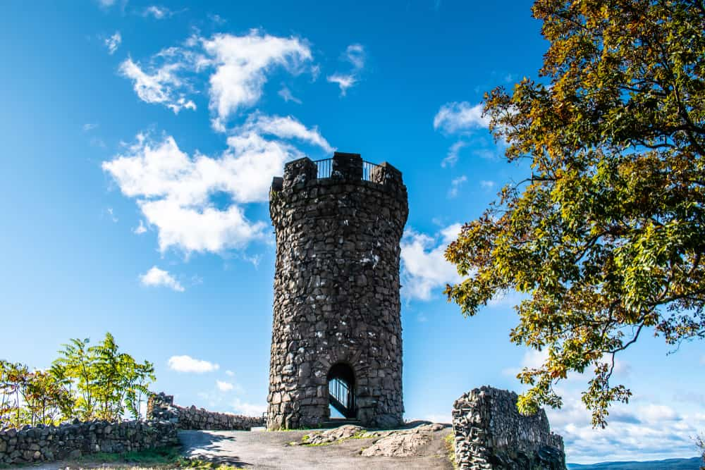 a bright blue sky with a few whispy clouds  and a stone castle turret in the foreground