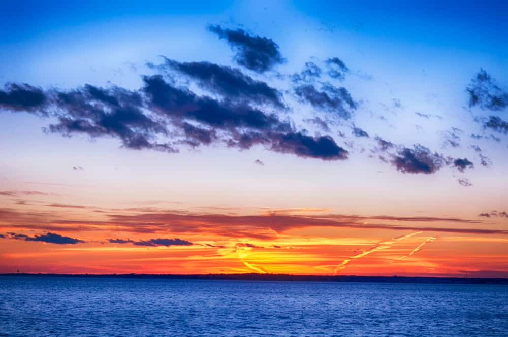 A multi colored sunset over the atlantic ocean on ocean drive in Newport Rhode Island.