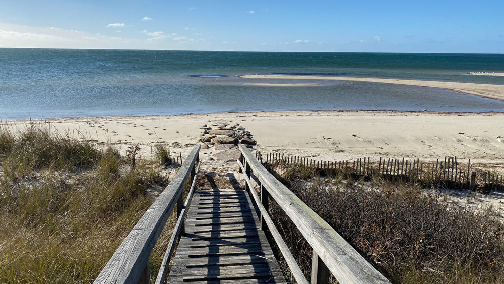 long wooden dock stretching out to empty beach cape cod usa
