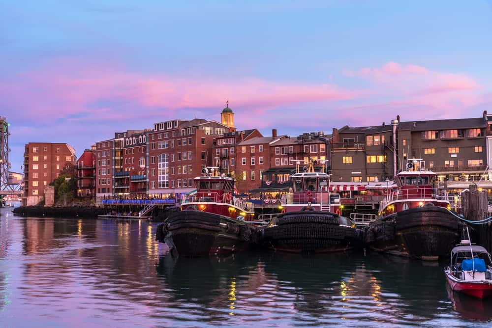 tug boats and a historic looking city seen from the harbor at dusk