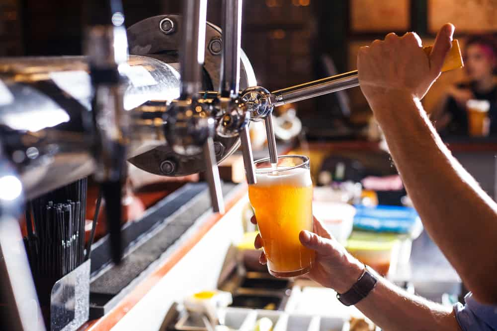 person pouring beer into pint glass