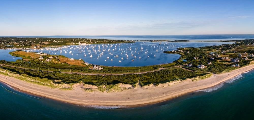 aerial shot of block island rhode island showing a wide stretch of beach and an inland pond harbor filled with boats