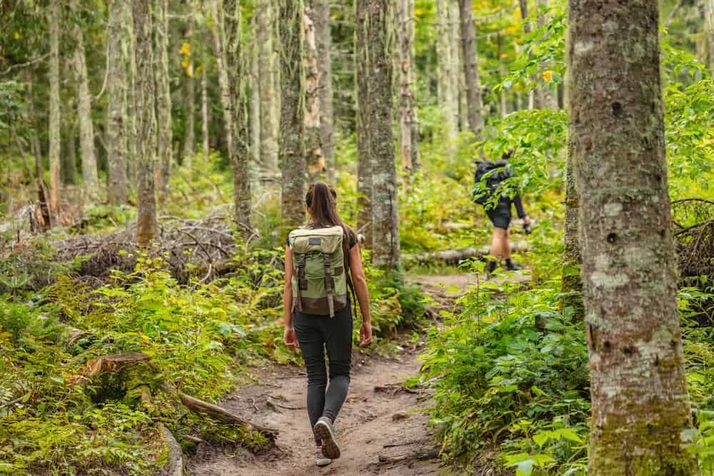 girl walking with backpack on a mud trail in forest