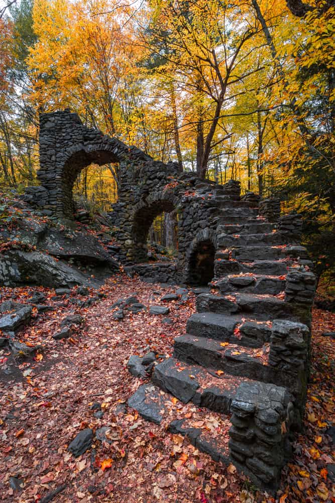 stone ruins of a curving stairway with arches in an autumnal forest