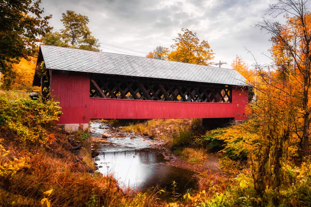 Red covered bridge surrounded by fall foliage.
