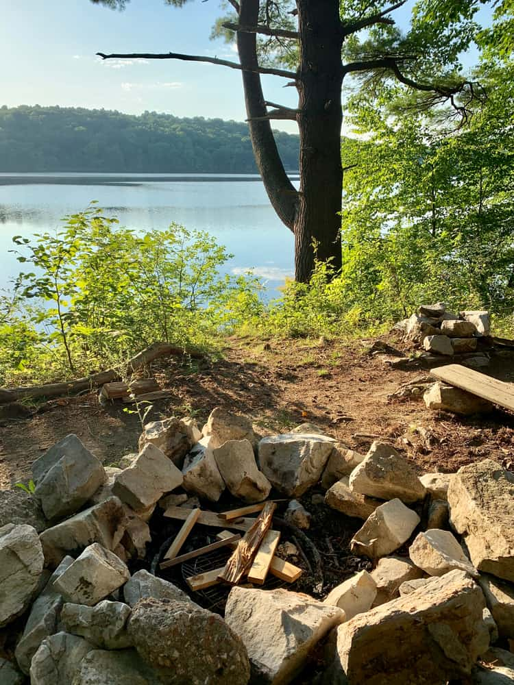 image of a lake seen from close to an unlit campfire, summer