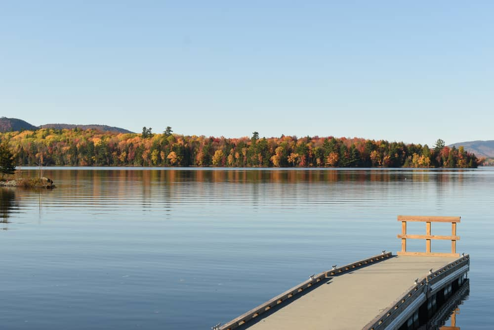 calm new hampshire lake bordered by early fall foliage