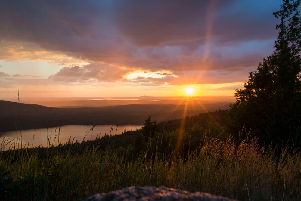 beautiful sunrise as seen from the top of a mountain in acadia maine