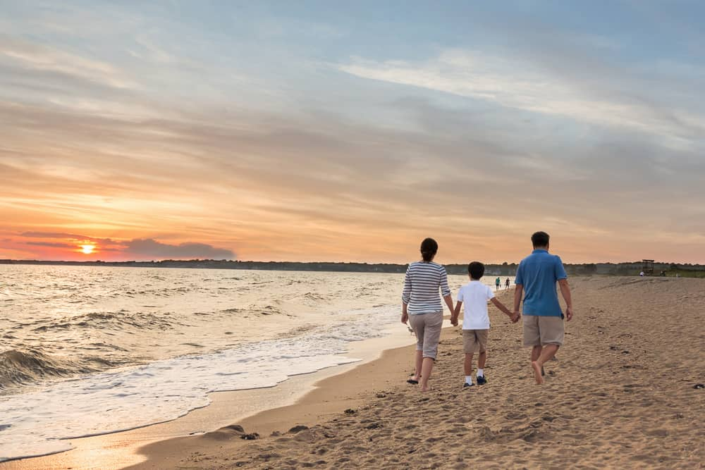 a small family walks hand in hand on a beach at sunset, connecticut
