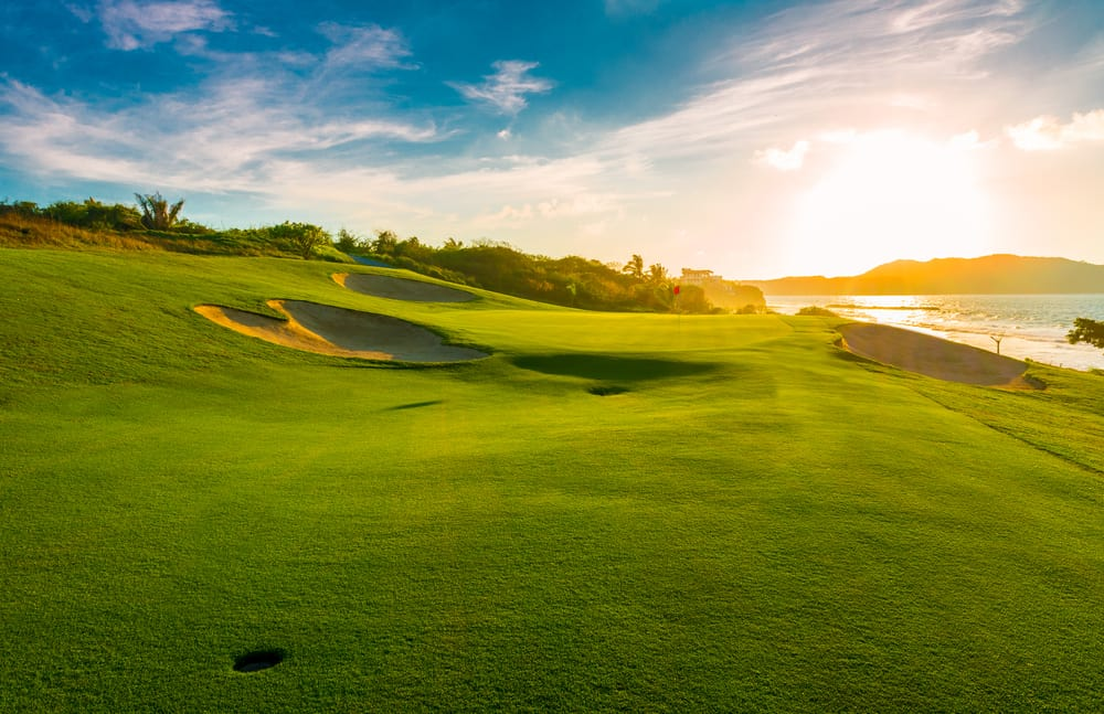rolling hills with golf course next to the water at sunset