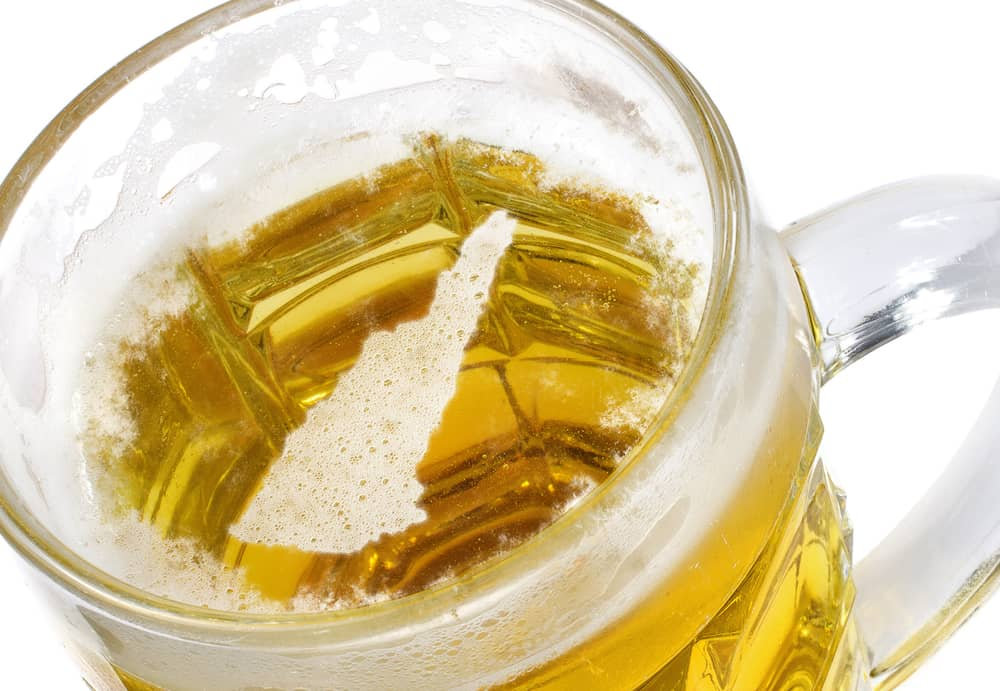 pint of golden beer with foam in the shape of the state of new hampshire