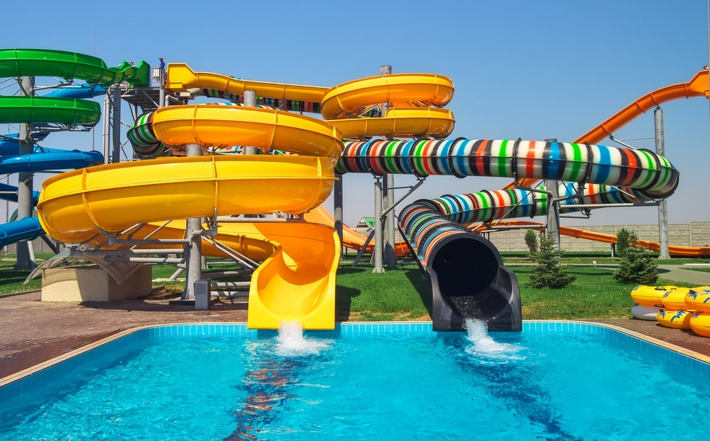 two colorful water slides emptying into a pool on a sunny day - water parks in new england hero image