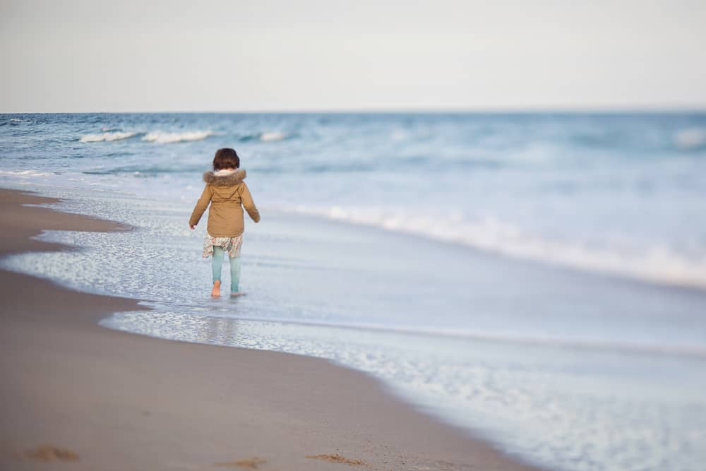 small girl walking along an empty beach - things to do in westerly RI