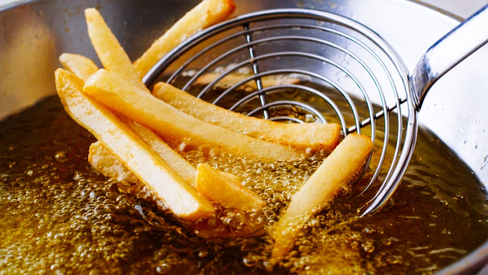 french fries getting dipped in golden grease