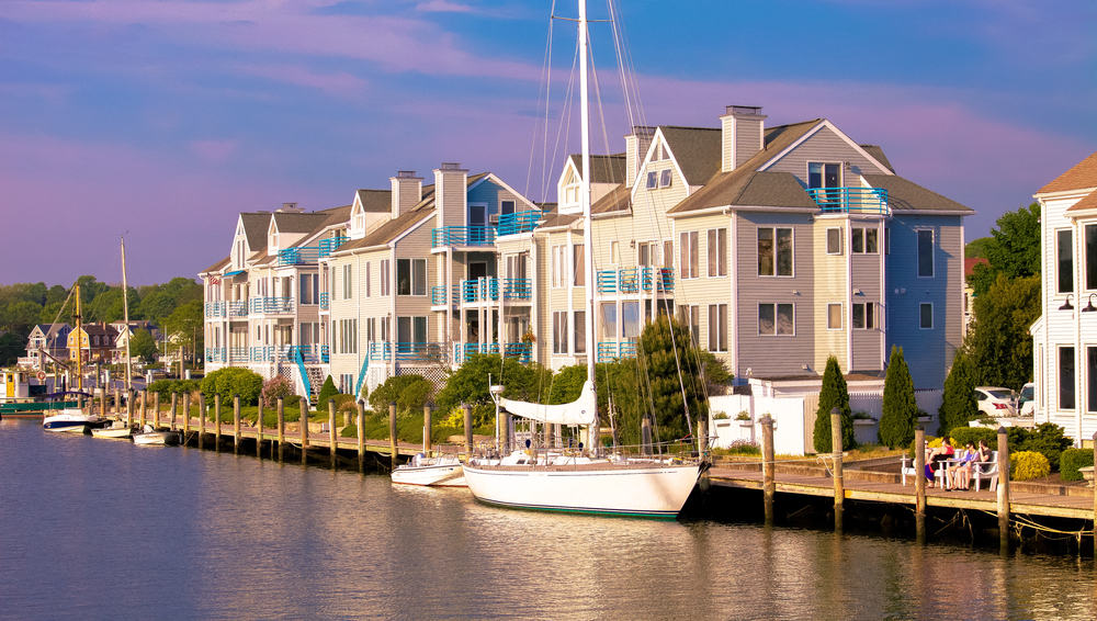 fancy homes and condos set next to an inlet with a sailboat moored nearby