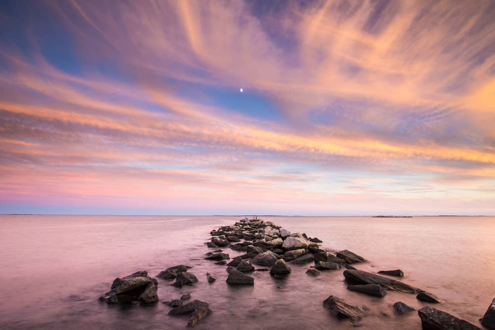 a pink and blue sunset seen over the water with rocks in foreground