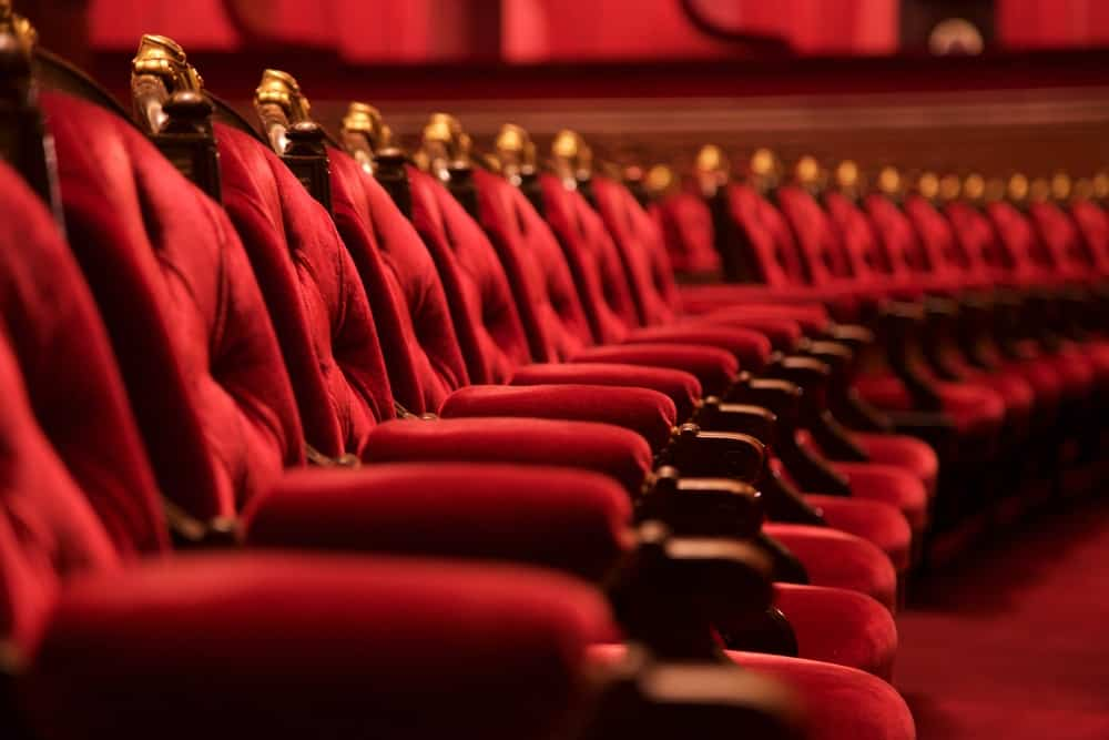 A row of bright red velvet chairs in a theater.