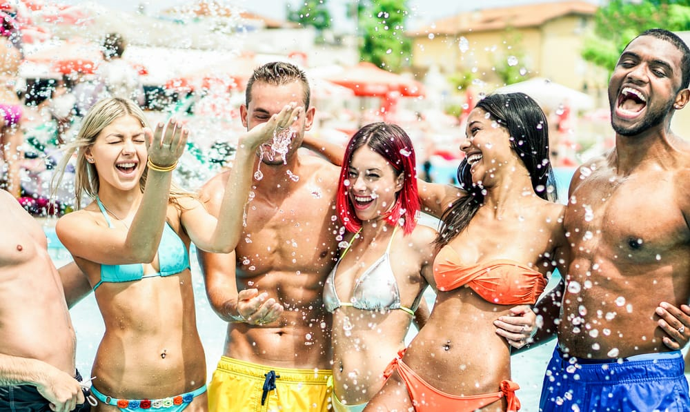 attractive young adults standing and laughing while being splashed in a water park