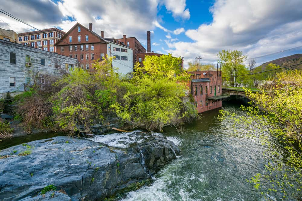 Rushing river going next to shops and green trees, one of the best things to do in Brattleboro.