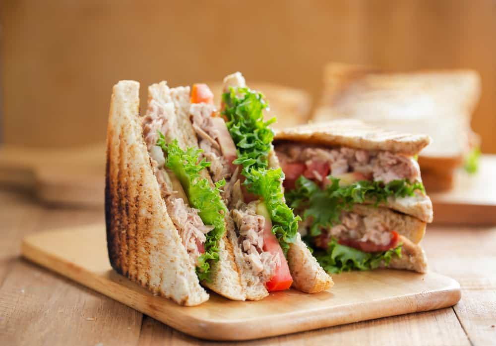 two sandwiches filled with meat, lettuce, and tomato