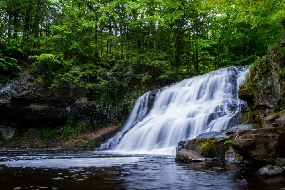 a gorgeous flowing waterfall in the height of summer