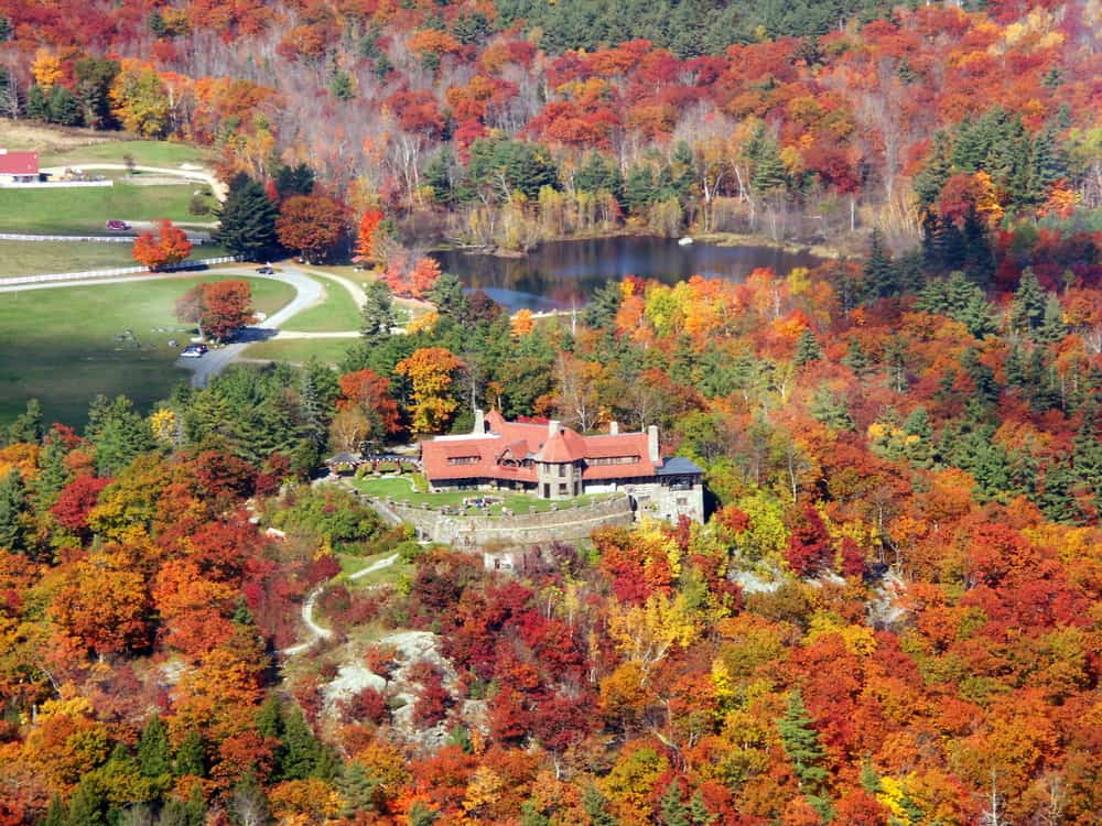 an overhead shot of a red roofed castle surrounded by fall foliage