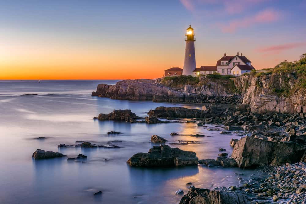 iconic new england maine lighthouse at sunset in back of rocky coast