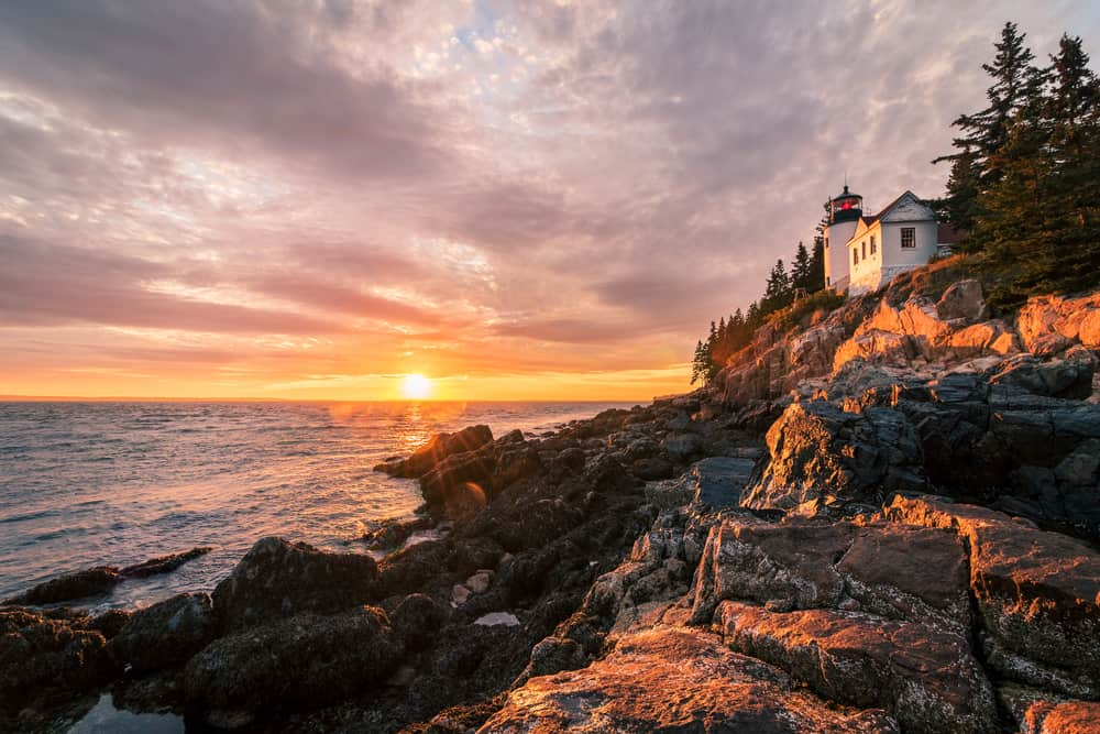 small white lighthouse perched on a high rocky cliff at sunset with pine trees behind it