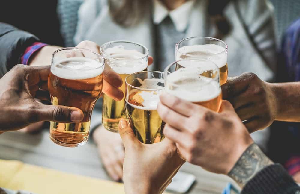 hands clinking pints of golden beer