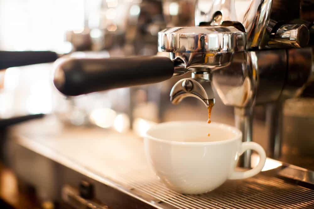 espresso coffee dripping into a small white cup