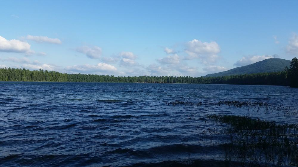 wide blue lake with mountains in distance on calm summer day new hampshire