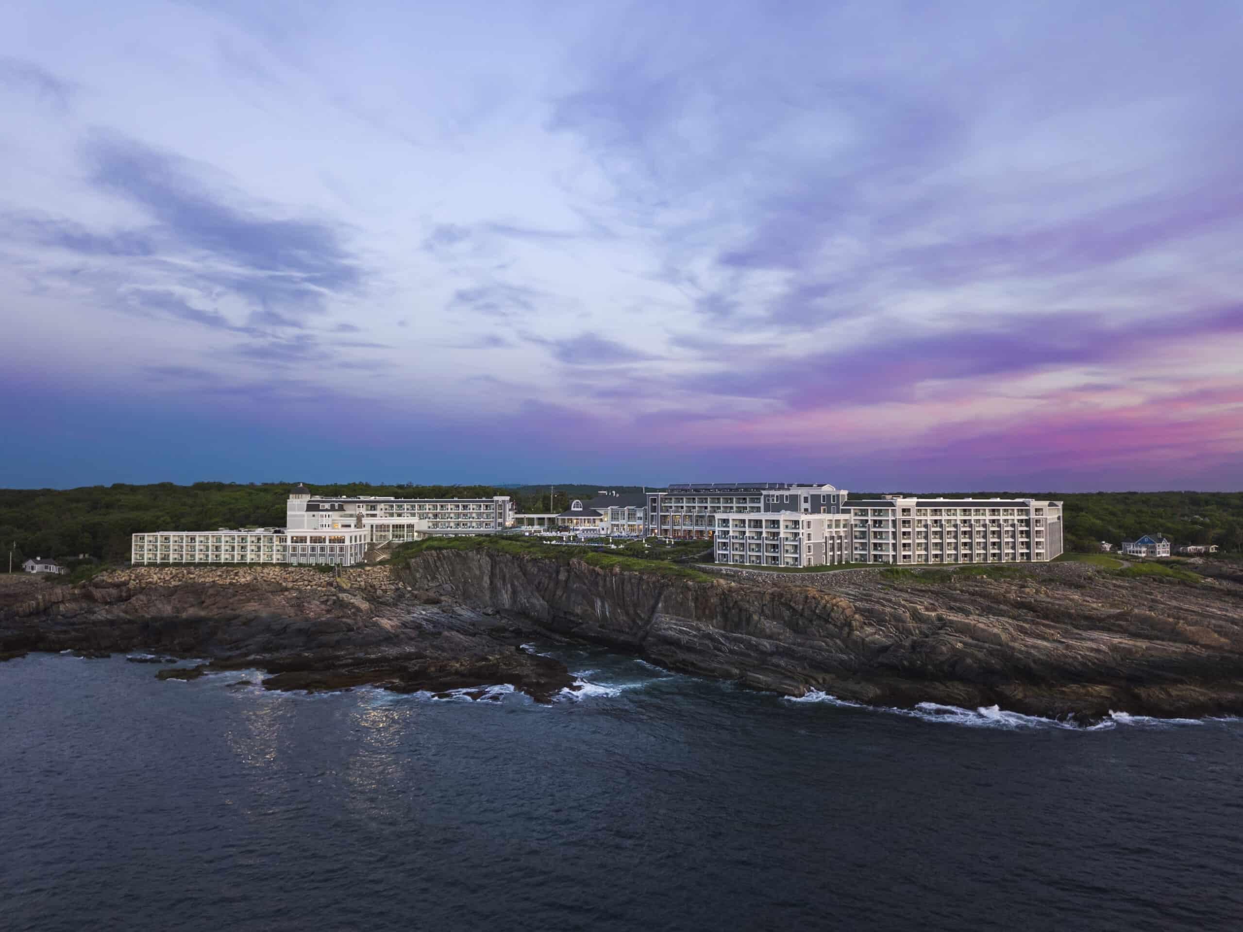 White hotel on the cliffs under a purple sunset