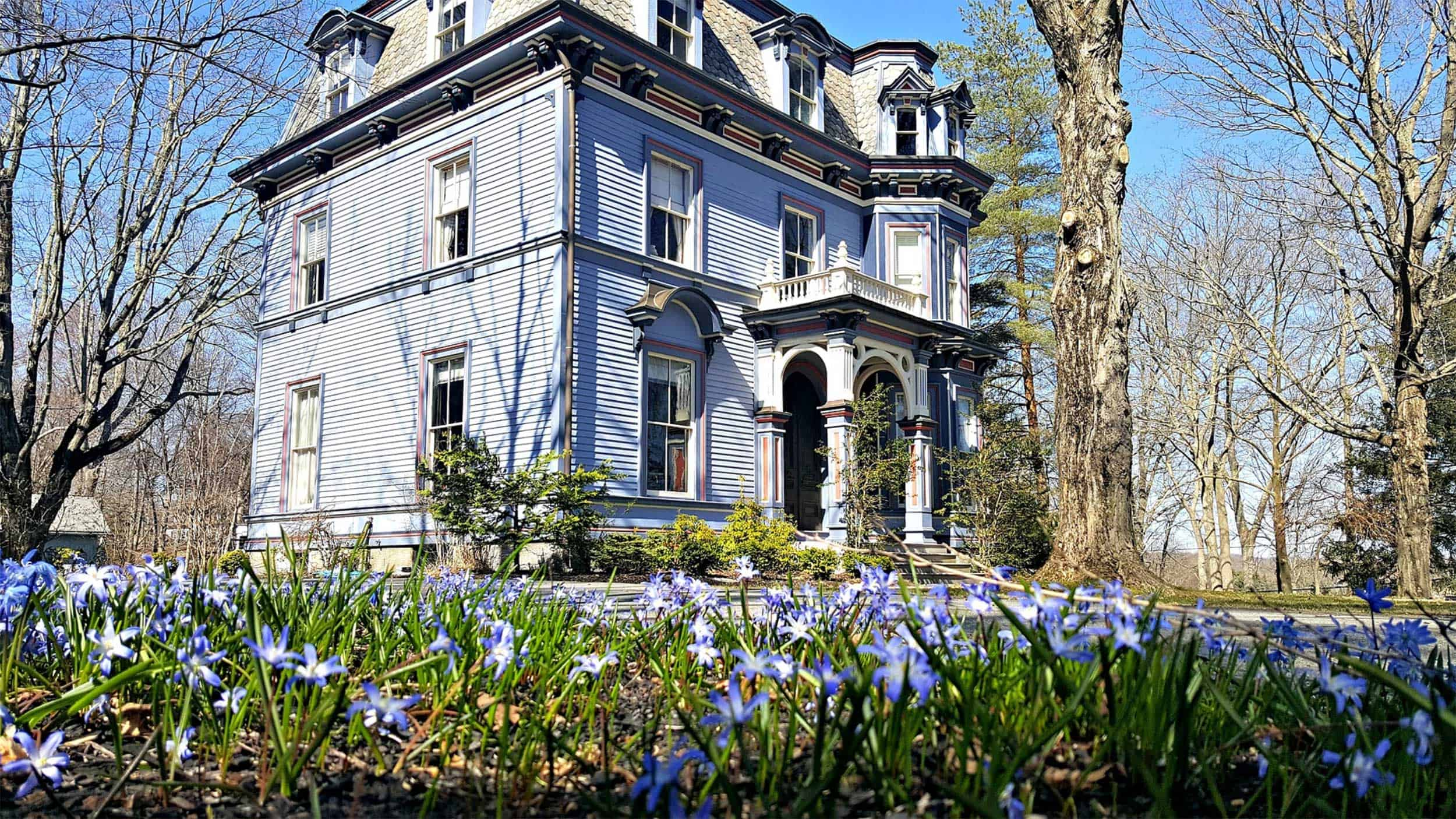 blue historic building surrounded by flowers, dreamiest connecticut bed and breakfasts