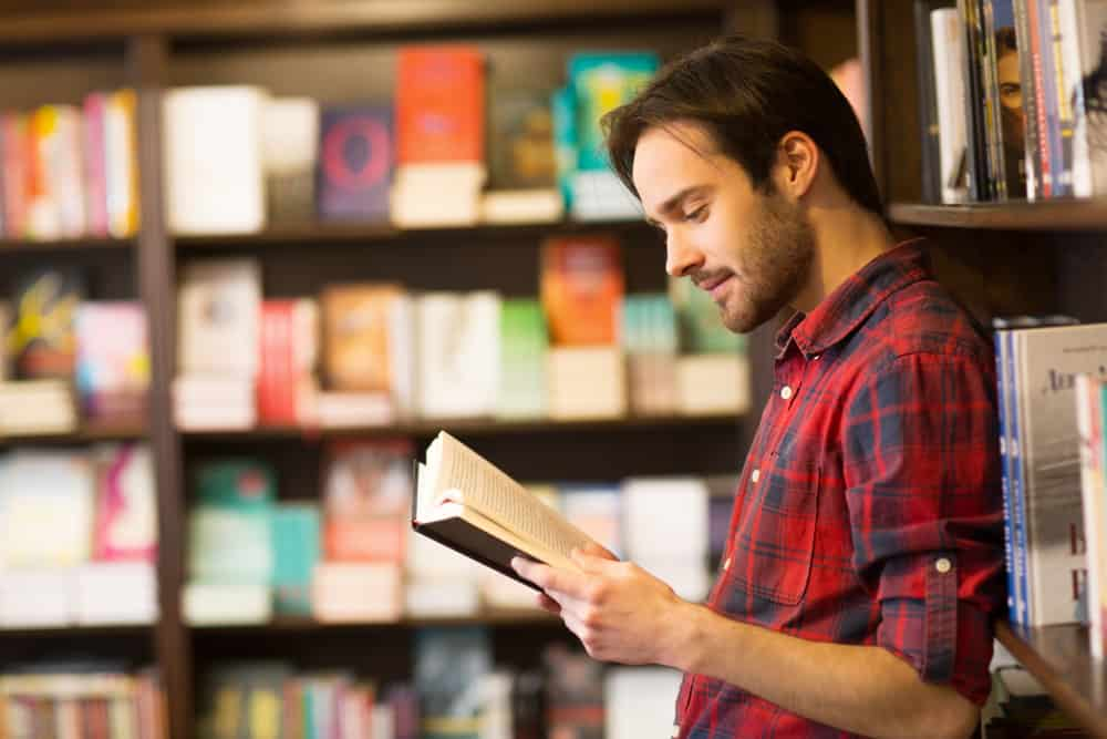 Man reading a book in a bookstore