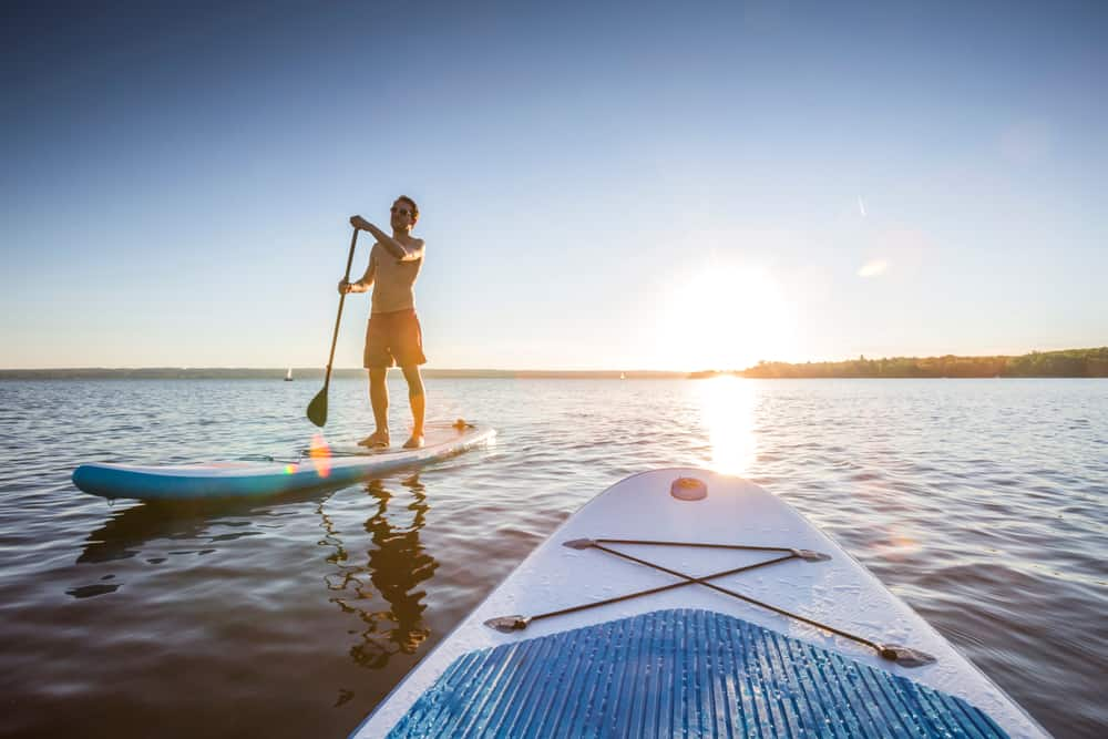 Guy paddleboarding while the sun is setting on a lake.