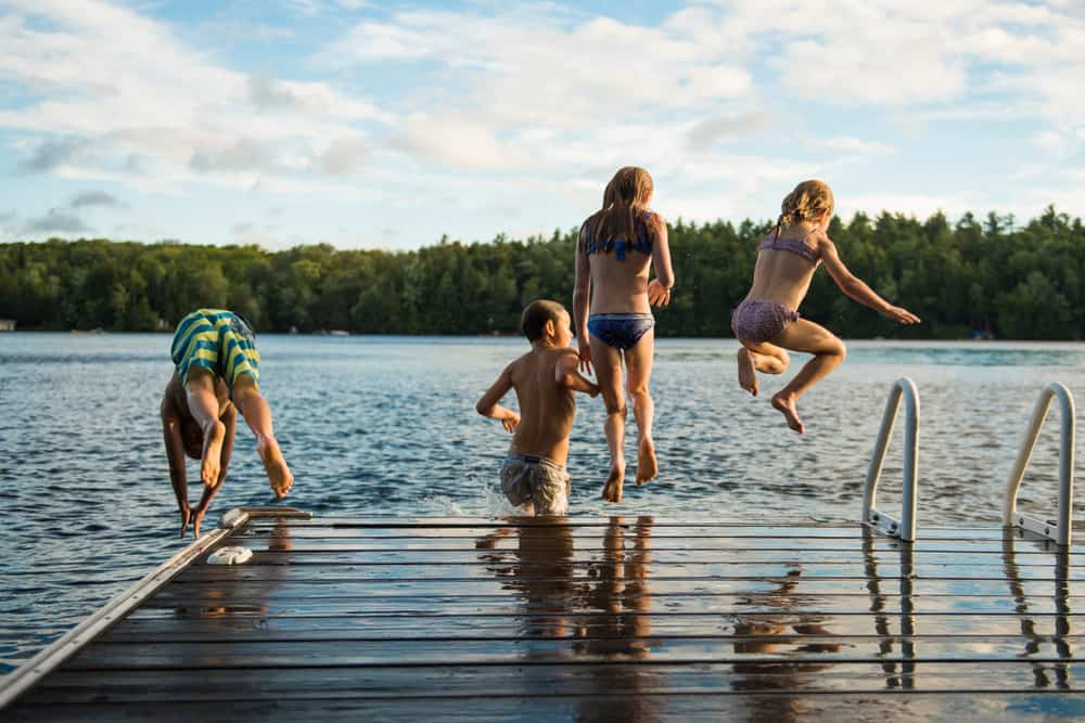 Group of children hopping off of a dock into a blue lake.