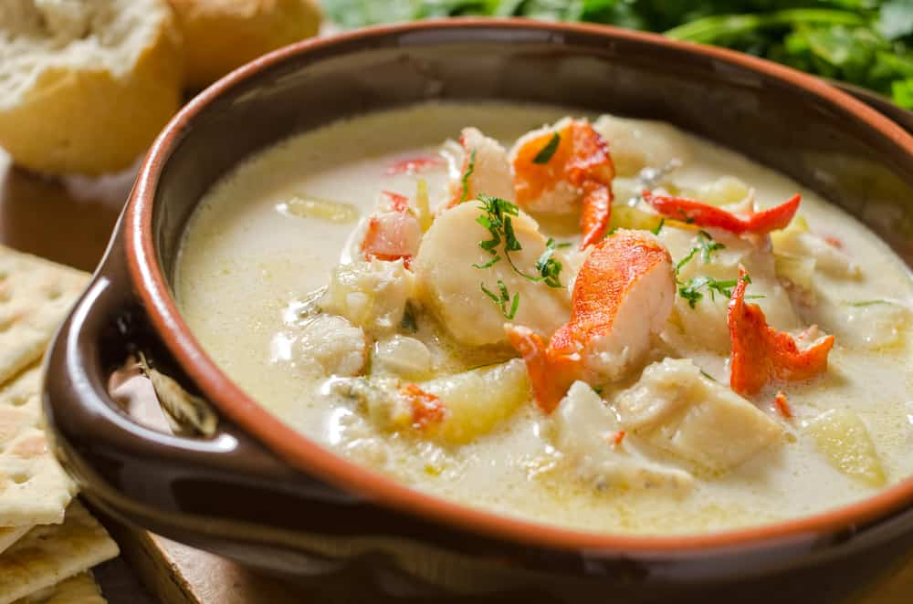 closeup of a seafood chowder with pieces of lobster on top