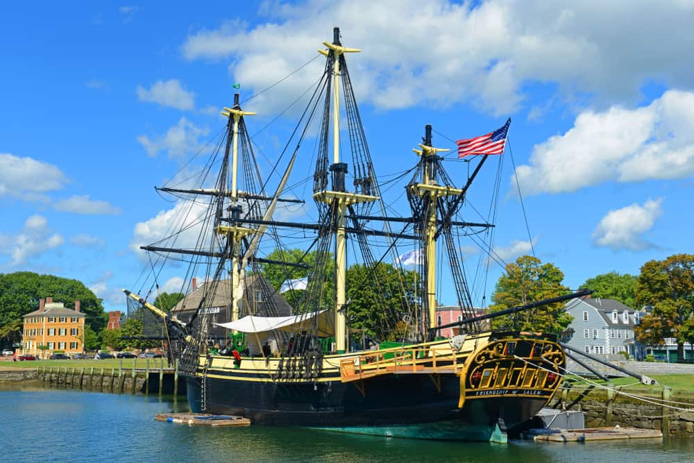 a historic tall ship with its sails down, sitting in a harbor on a sunny day, salem massachusetts