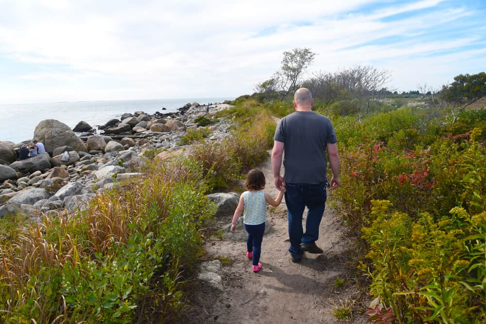 Father and daughter walking on a trail by the beach