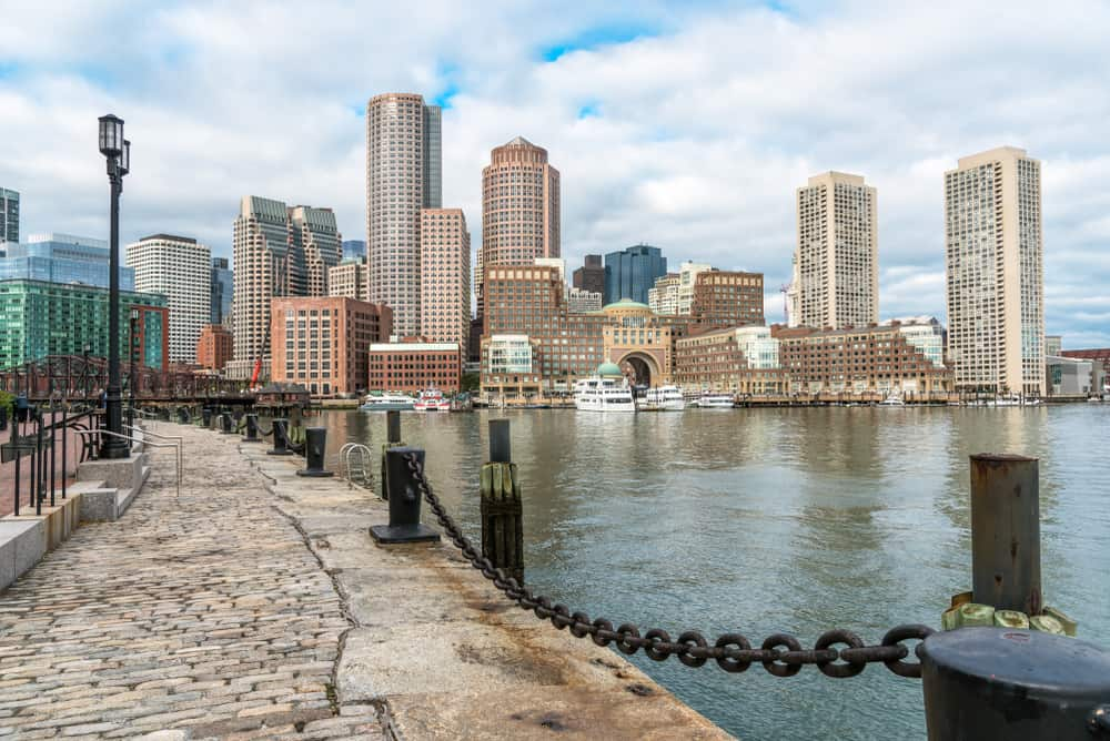 Stone walkway next to the harbor and the Boston skyline, best walking tours in Boston
