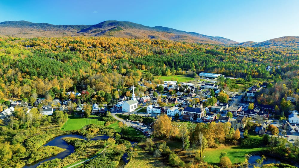 Small town surrounded by mountains under a blue sky, hiking in Stowe