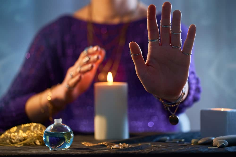 a fortune teller sits with a candle and various accessories with her palm facing towards the camera