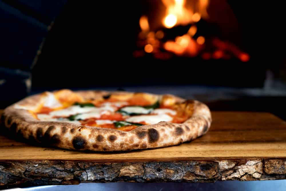 Pizza on a slab of wood with fire in the background