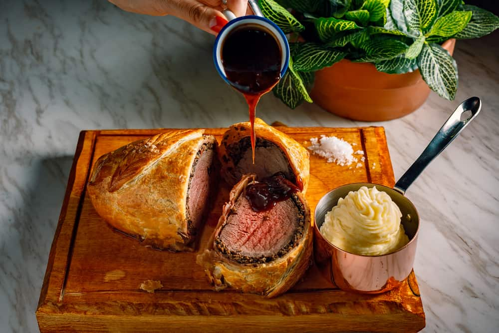Beef wellington cut open with mashed potatoes