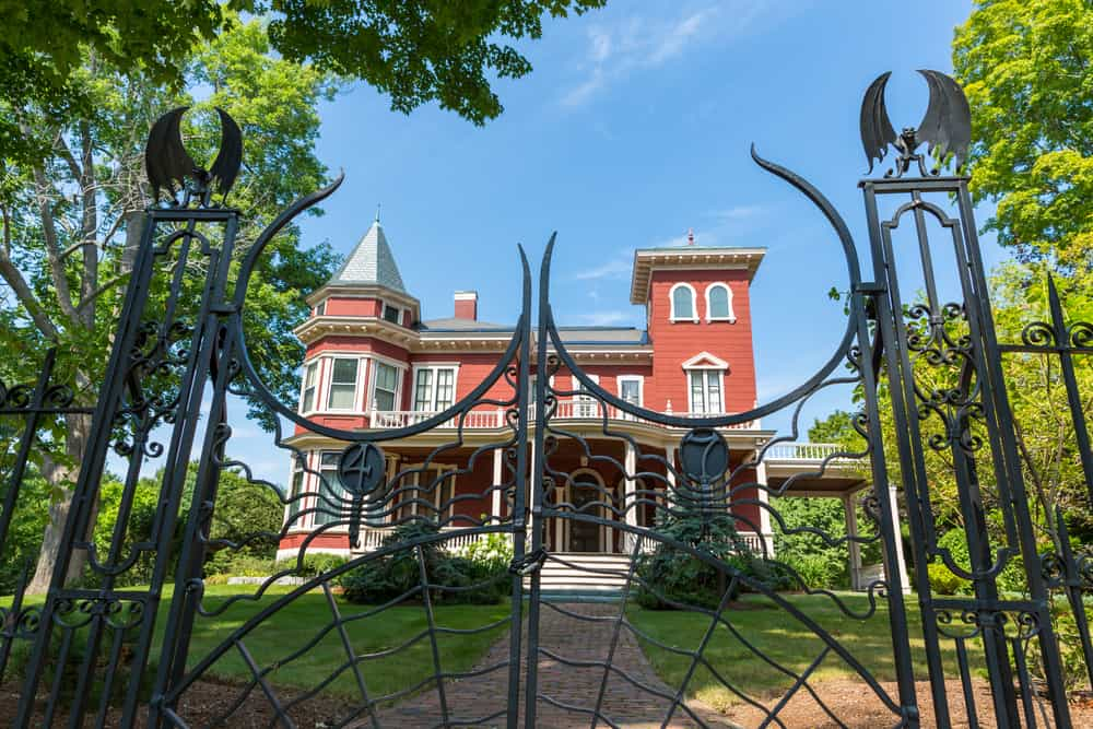 Stephen King's mansion with a spider fence in front, in Stephen King's Maine.