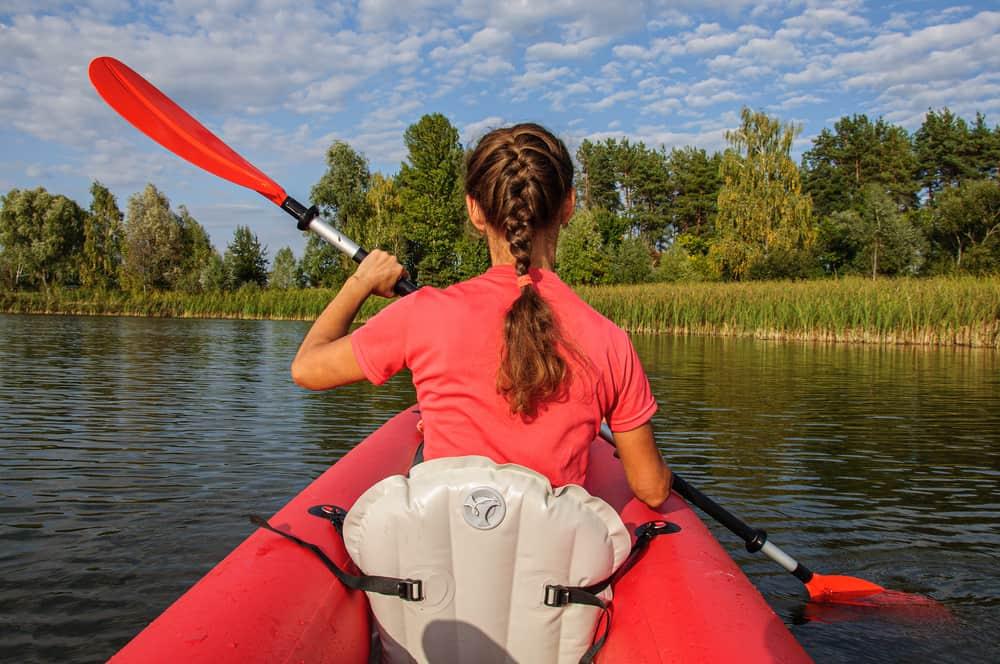 Girl kayaking in a red kayak on a lake.