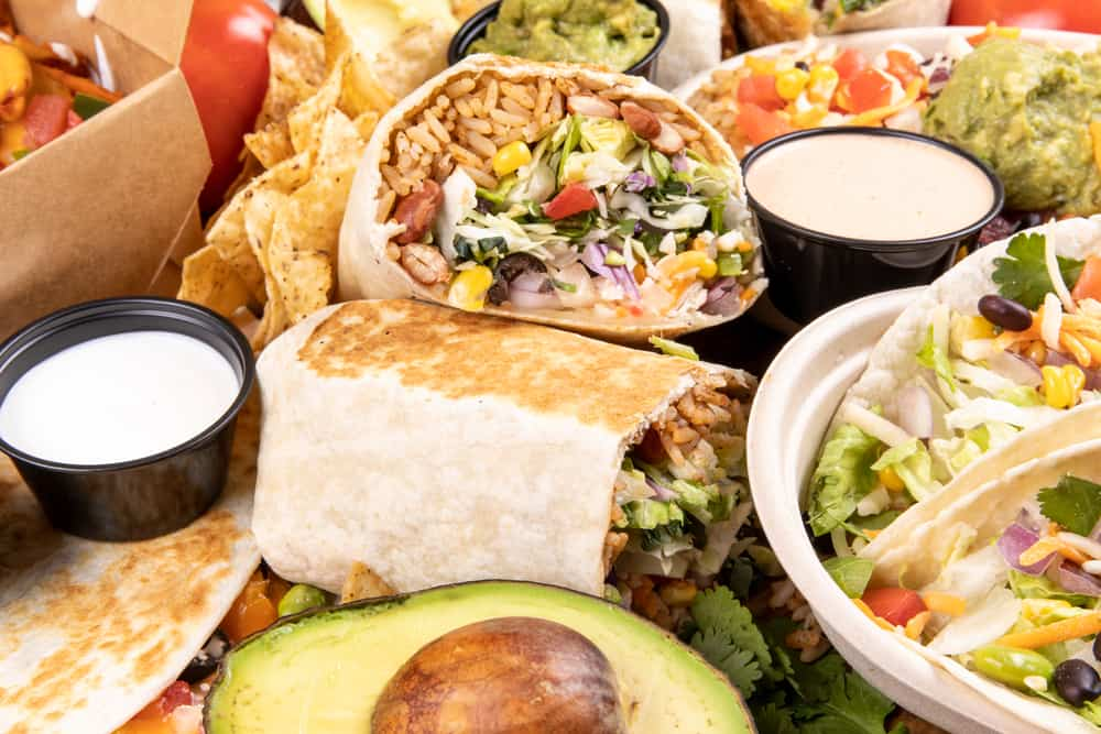 Cut in half burrito surrounded by avocadoes, sour cream, and other foods, best restaurants in north conway