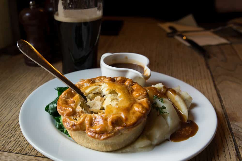 a dinner plate with a small pot pie, gravy, and a dark beer in the back