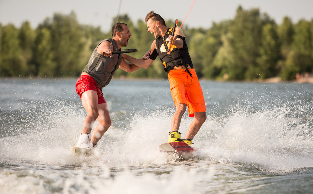 Two guys water skiing and having fun on a lake.