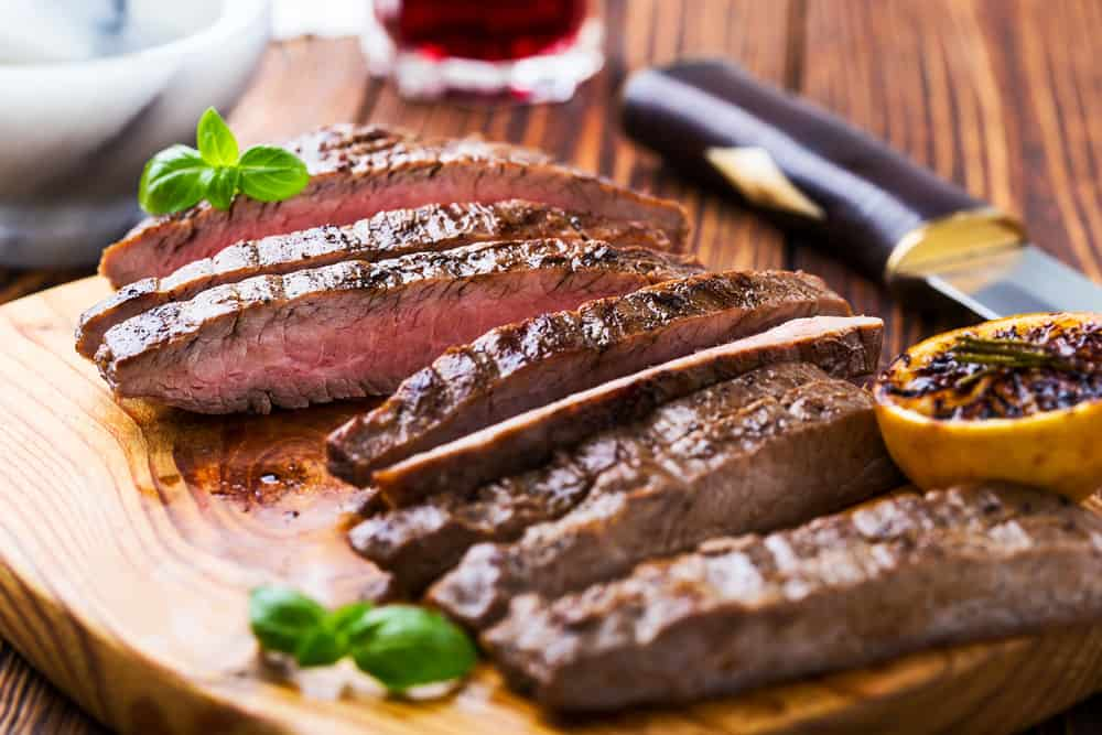 Flank steak chopped up on a piece of wood